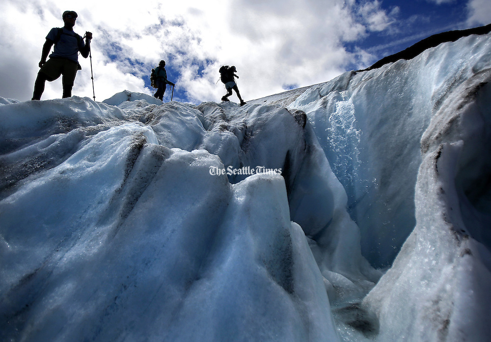 Research assistants navigate around a supraglacial stream on Sholes Glacier as they make measurements to assess the volume lost.<br /> <br /> Sy Bean / The Seattle Times