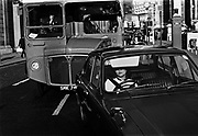 Car & bus waiting for traffic lights, Bank, London. Coming and Going is a project commissioned by the Museum of London for photographer Barry Lewis in 1976 to document the transport system as it is used by passengers and commuters using public transport by trains, tubes and buses in London, UK.