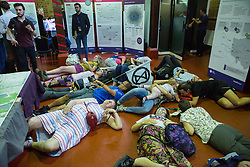 London, UK. 18 July, 2019. Climate activists from Extinction Rebellion stage a die-in at Heathrow's consultation event for its preferred 'master plan' in Lambeth in protest against plans for a third runway at Heathrow airport and to highlight Heathrow airport's major contribution to climate change.