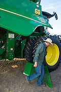 John Barrett and his assistant Jonathan clean a 2014 John Deere combine each morning during the wheat harvest by opening the panels and blowing out the dust, removing debri, and adjusting tensioners.