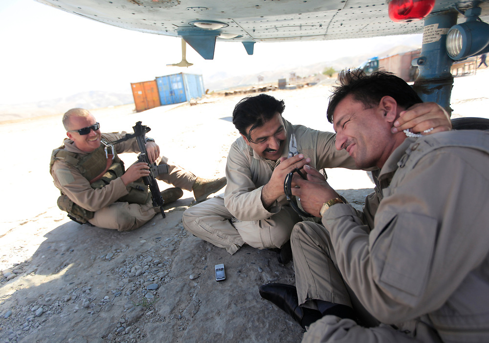 8/24/09 2:58:54 AM -- Kabul, Afghanistan<br />  -- Afghan Army Air Corps Mentors in Afghanistan -- Afghan Air Corps pilots Lt. Saeed Fazil , right, laughs as General Amin Jan, center, of the Afghan 377th Rotary Wing Squadron jokes about pulling a tooth along with mentor USAF TSgt. Ty Kobza, while waiting for repairs to be completed on their Mi-17 helicopter in the northern Afghan town of Fayzabad.--<br /> <br /> Photo by Jack Gruber, USA TODAY Staff