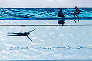 Seen from the ground, swimmers enjoy the waters of the Sky Pool, a 25 metres-long transparent water pool bridging two 10-storey residential towers 35 metres above the ground, the largest freestanding acrylic pool structure in the world at EcoWorld Ballymore's new Embassy Gardens development in Nine Elms, on 3rd June 2021, in London, England.