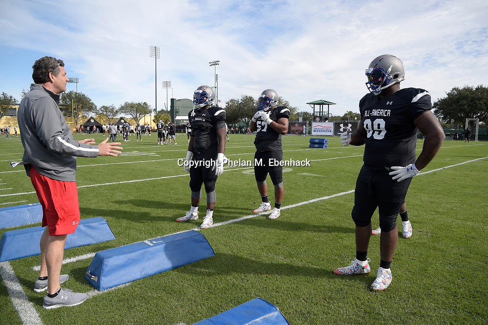 Team Armour defensive coach Mike Golic, left, instructs defensive linemen Akial Byers, Greg Rogers, second from right, and Marvin Wilson (99) during a practice for the Under Armour All-America football game in Lake Buena Vista, Fla., Friday, Dec. 30, 2016. (Photo by Phelan M. Ebenhack)