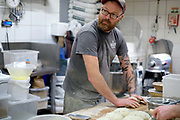 Baker Philip Clayton kneading sourdough bread at the Haxby Bakehouse, Yorks artisan bakery in Haxby, North Yorkshire, United Kingdom on 10th February 2017. Haxby Bakehouse make bread using traditional methods of slow fermentation. They use low yeasted overnight sponges, natural sourdough levain or a combination of the two. This means the bread they produce is full of flavour without the use of any artificial flour improvers, preservatives or emulsifiers.