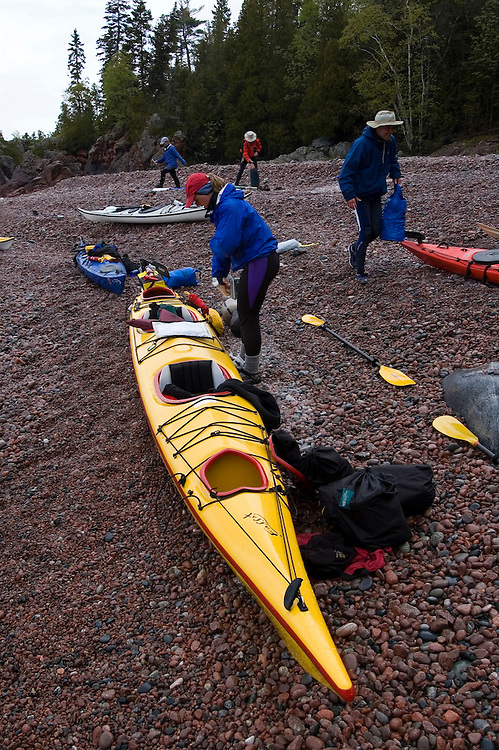 A group of sea kayakers load their boats in Lake Superior Provincial Park near Wawa Ontario Canada.