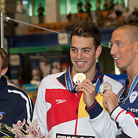 Bronze medalist Yauhen Tsurkin (L) of Belarus, gold medalist Rafael Munoz Perez (C) of Spain and silver medalist Frederick Bousquet (R) of France celebrate their victory during the Men's 50m Butterfly final of the 31th European Swimming Championships in Debrecen, Hungary on May 22, 2012. ATTILA VOLGYI