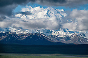 At 20,310 feet elevation or 6191 m, the peak of Denali (previously known as Mount McKinley) is the highest mountain in North America. Denali National Park, Alaska, USA. When measured from its base, it is earth's tallest (most prominent) mountain on land. Denali is a granitic pluton uplifted by tectonic pressure while erosion has simultaneously stripped away the softer surrounding sedimentary rock.
