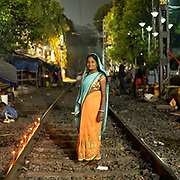 A woman living next to the train rails. Slum area located along the railway track.