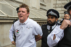 Whitehall, London, September 9th 2015.  A Palestinian supporter is arrested as pro Palestinian and Israeli counter-protesters clash in Whitehall as the Palestinian Solidarity campaign demands the arrest of Israel's PM Benyamin Netanyahu for war crimes in the 2014 war with Palestinians in Gaza.  // Contact: paul@pauldaveycreative.co.uk Mobile 07966 016 296