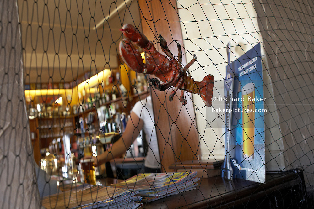 Plastic lobster and net at the bar of The Ship and Lobster, an 1832 Dickensian pub reflecting the shellfish trade on the Thames