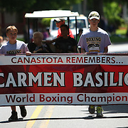 A salute to Hall of Fame boxer Carmen Basilio is seen on a banner in the parade of champions during the 2013 International Boxing Hall of Fame induction ceremony  on Sunday, June 9, 2013 in Canastota, New York.  Basilio passed away this year.  (AP Photo/Alex Menendez)