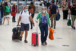 © Licensed to London News Pictures. 08/07/2021. London, UK. A couple wearing face coverings with suitcases in Waterloo Station. Transport Secretary, Grant Shapps said to the MPs, that fully vaccinated adults and all children will no longer have to quarantine on their return from amber list countries from 19 July 2021.  Photo credit: Dinendra Haria/LNP