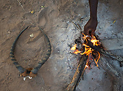 Gabriel and family cooking and eating gazelle meat that he hunted. At the Hadza camp of Senkele.