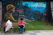 Bolivia.La Paz . June 2013. Wall paintingcelebrating industry and with two people sat on a bench, one reading a newspaper.