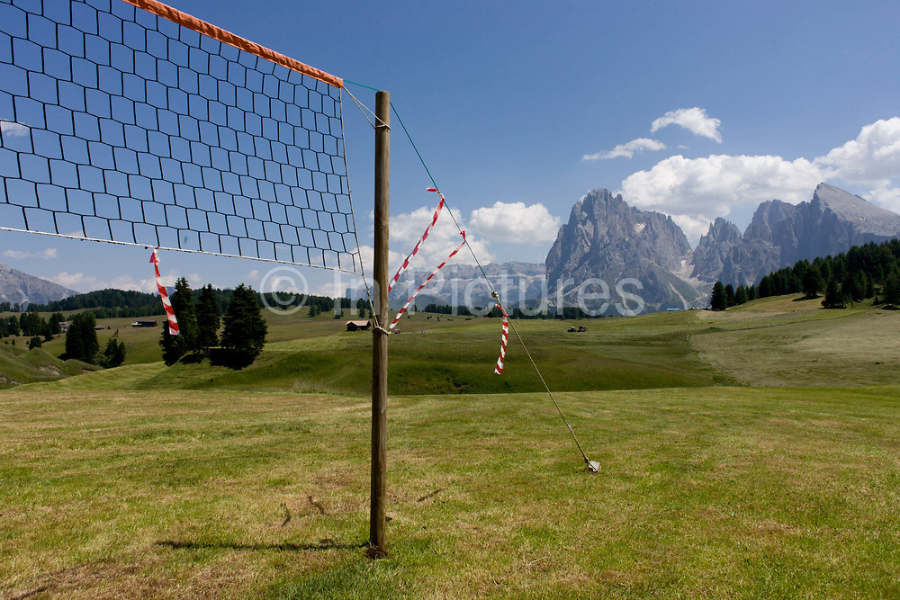 Netball net landscape on the Alpe di Siusi (German: Seiser Alm) plateau, above the South Tyrolean town of Ortisei-Sankt Ulrich in the Dolomites, Italy. Walking along one of the dozens of paths, hikers and their children are treated to panoramic views of the peaks and many platy areas to encourage a younger generation into the wilderness. The Alpe di Siusi is the biggest high-alpine pasture in Europe with a surface of 57 km² and its altitude range from 1680 to 2350 m above sea level. This high-alpine pasture is located in the heart of the Dolomites surrounded by the Sasso Lungo Mountain Group, the Sciliar Nature Park, and the Catinaccio Mountain Group, the Northern Alps and the Sciliar Mountain Massif with Santner Peak.
