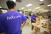 FedEx employee Guy Gerodinas files down the edges of a playhouse's windows to remove any splinters at the Habitat For Humanity shop in Milpitas, Calif., on Sept. 11, 2012.  Photo by Stan Olszewski/SOSKIphoto.