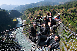 Chris Drew, Christopher Galley, Chris Marino, Doug Wothke, Jason Adamski, Mikey Revolt, Pat Patterson, Rob Galen, Tim Statt and Motorcycle Sherpa's Bear Haughton ham it high up on the Kushma - Gyadi suspension bridge over the Modi River (the highest, at 384 feet, and longest, at 1,128 feet, suspension bridge in Nepal) during the Ride to the Heavens motorcycle adventure in the Himalayas of Nepal. On the sixth day of riding, we went from Tatopani to Pokhara. Saturday, November 9, 2019. Photography ©2019 Michael Lichter.