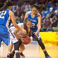 Tohatchi Cougar Shynelle Dawes (20) maintains possession of the ball being blocked by Laguna Acoma Hawk Deja Kie-Lorenzo (32) and Talia Paytiamo (22) during the playoff game at the Santa Ana Star Center Tuesday.