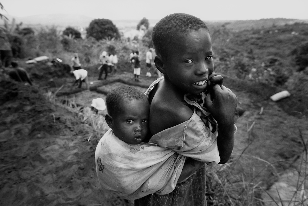 Eight-year-old Syombua, carrying his brother Kilonzo in front of the Habitat house being built for his family outside of Nairobi, Kenya.