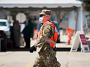 """26 APRIL 2020 - DES MOINES, IOWA: A soldier with the Iowa Army National Guard walks past the COVID-19 drive through testing site in Des Moines. Iowa started mass testing Saturday, with a drive through testing site in a parking lot in downtown Des Moines. The testing this weekend is considered a """"soft opening"""" for the program and tests were reserved for medical professionals and first responders. Despite numerous outbreaks in meat packing plants throughout Iowa, members of the public have not been able to get tested. On Saturday, 25 April, there were 5,092 confirmed cases of COVID-19 (Coronavirus / SARS-CoV-2) in Iowa (an increase of 647 since Friday, April 24) and 112 deaths in Iowa caused by COVID-19.         PHOTO BY JACK KURTZ"""