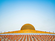 """11 FEBRUARY 2016 - KHLONG LUANG, PATHUM THANI, THAILAND: Buddhist monks pray in their seats on the pagoda during the Makha Bucha Day service at Wat Phra Dhammakaya.  Makha Bucha Day is a public holiday in Cambodia, Laos, Myanmar and Thailand. Many people go to the temple to perform merit-making activities on Makha Bucha Day, which marks four important events in Buddhism: 1,250 disciples came to see the Buddha without being summoned, all of them were Arhantas, or Enlightened Ones, and all were ordained by the Buddha himself. The Buddha gave those Arhantas the principles of Buddhism. In Thailand, this teaching has been dubbed the """"Heart of Buddhism."""" Wat Phra Dhammakaya is the center of the Dhammakaya Movement, a Buddhist sect founded in the 1970s and led by Phra Dhammachayo. Makha Bucha Day is one of the most important holy days on the Thai Buddhist calender.      PHOTO BY JACK KURTZ"""