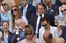 © Licensed to London News Pictures. 12/07/2019. London, UK. Hugh Grant and Anna Grant watch centre court tennis in the royal box on Day 11 of the Wimbledon Tennis Championships 2019 held at the All England Lawn Tennis and Croquet Club. Photo credit: Ray Tang/LNP