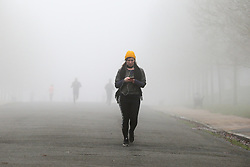 © Licensed to London News Pictures. 28/12/2020. London, UK. A woman walking in dense freezing fog in Finsbury Park, north London as many parts of the UK wakes to further freezing temperatures. Photo credit: Dinendra Haria/LNP