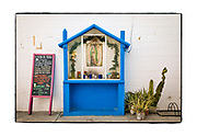 """SHOT 2/16/19 5:23:49 PM - A small blue capilla outside the market in Tulum, Mexico. Capillas, or tiny chapels, are common along the roads and highways as well as in town all over Mexico, which is largely Catholic. The capillas are often dedicated to certain patron saints, such as Nuestra Senora de Guadalupe. Often times they contain prayer candles, pictures, personal artifacts or notes. Tulum (sometimes Tulum Pueblo) is the largest community in the municipality of Tulum, Quintana Roo, Mexico. It is located on the Caribbean coast of the state, near the site of the archaeological ruins of Tulum. The community had a 2010 census population of 18,233 inhabitants. As recently as the early 1990s Tulum Pueblo was a quiet village about 2 miles from the archaeological site, and tourism outside of the ruins was limited to a few small shops and simple cabanas on the beach. More recently the """"hotel zone"""" of boutique hotels along the Tulum beach has grown to more than 70 small hotels with an upscale bohemian vibe to many of the properties. (Photo by Marc Piscotty / © 2019)"""