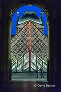 France, Paris (75), Louvre Museum at night with Pyramid illuminated. Two African tchotchke sellers.