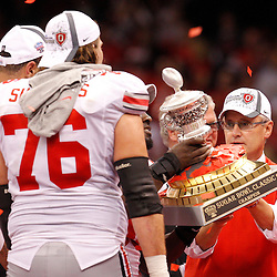 January 4, 2011; New Orleans, LA, USA;  Ohio State Buckeyes head coach Jim Tressel hands the Sugar Bowl Classic championship trophy to players following a win over the Arkansas Razorbacks in the 2011 Sugar Bowl at the Louisiana Superdome.Ohio State defeated Arkansas 31-26. Mandatory Credit: Derick E. Hingle