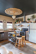 The kitchen's anchor features include a large round rug ($25 thrift store buy) fastened to the ceiling around the light fixture and the wall that Liz painted some of her favorite plants on (free handed - without stencils). It is a social room with inviting sitting areas as well. <br /> Image by Shauna Intelisano
