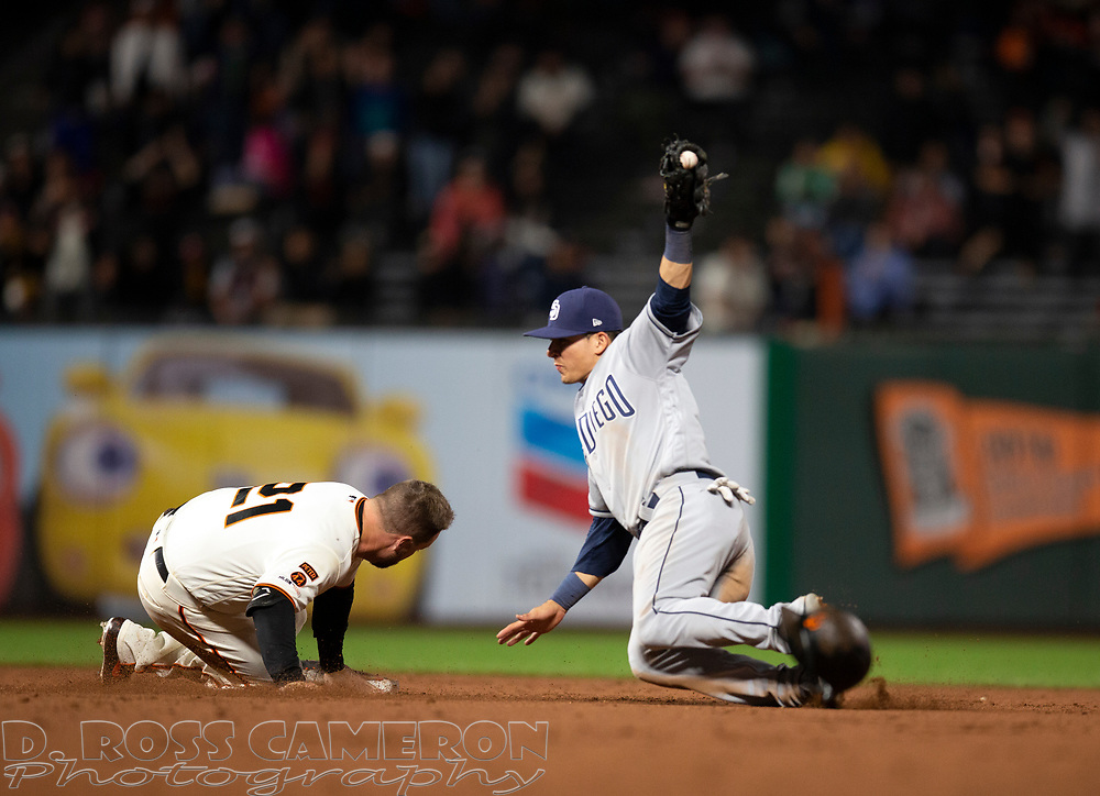 San Francisco Giants' Stephen Vogt (21) slides in safely with an RBI double as San Diego Padres shortstop Luis Urias (9) reaches for the late relay during the ninth inning of a baseball game against the San Diego Padres, Thursday, Aug. 29, 2019, in San Francisco. The Padres won 5-3. (AP Photo/D. Ross Cameron)