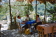 People sitting at table of shady outdoor cafe island of Ibiza, Balearic Islands, Spain,  1950s