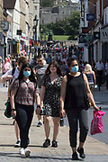 Shoppers, some of whom wearing face coverings, are pictured close to Windsor Castle on Freedom Day, when the UK government lifted almost all remaining Covid-19 restrictions in England, on 19th July 2021 in Windsor, United Kingdom. Social distancing restrictions have been removed and face coverings are no longer required by law, although their use is recommended in crowded and enclosed spaces. Cases of the coronavirus are now expected to surge across the UK, which currently has the highest rate of daily recorded Covid-19 cases in the world.
