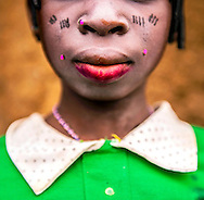 Umou, 16, puts on her best clothes and lipstick for a baby naming ceremony in a small village in the Kalalé District of Benin. She is one of the few girls who goes to school past a young age. <br /> <br /> The economy is mainly based on agriculture with more than 95% of the population involved with farming. Despite its great potential, crop production in Kalalé remains weak and easily influenced by natural conditions. There is precious little rainfall during the six-month dry season that runs from November to April each year. During the dry season, the land of Kalalé is parched and its people are hungry. Malnutrition is widespread and most girls won't get access to education because the most pressing challenge for all the people of Kalalé is having enough food to eat. (photo by Ami Vitale)