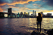 A girl stares at the Manhattan skyline and the Brooklyn bridge at sunset from DUMBO, Brooklyn.