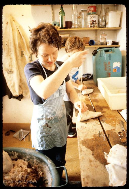 Woman sews closed bag of intestinal skin stuffed w/ lamb fat & blood, a delicacy called slatur. Iceland