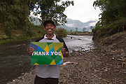 Abdul Quddus Ali, 36 (left), Secretary of Sembalun Lawang's emergency preparedness team, poses for a photograph holding a 'Thank you' sign. He is standing on the embankment on the Sempronan river in Sembalun Lawang, Sembalun district, East Lombok, West Nusa Tenggara province. This river was widened and deepened to prevent recurrent flooding. The village's emergency preparedness team collected data about land ownership on the banks of the river and proposed the project to the village government. Then the district government executed the work.