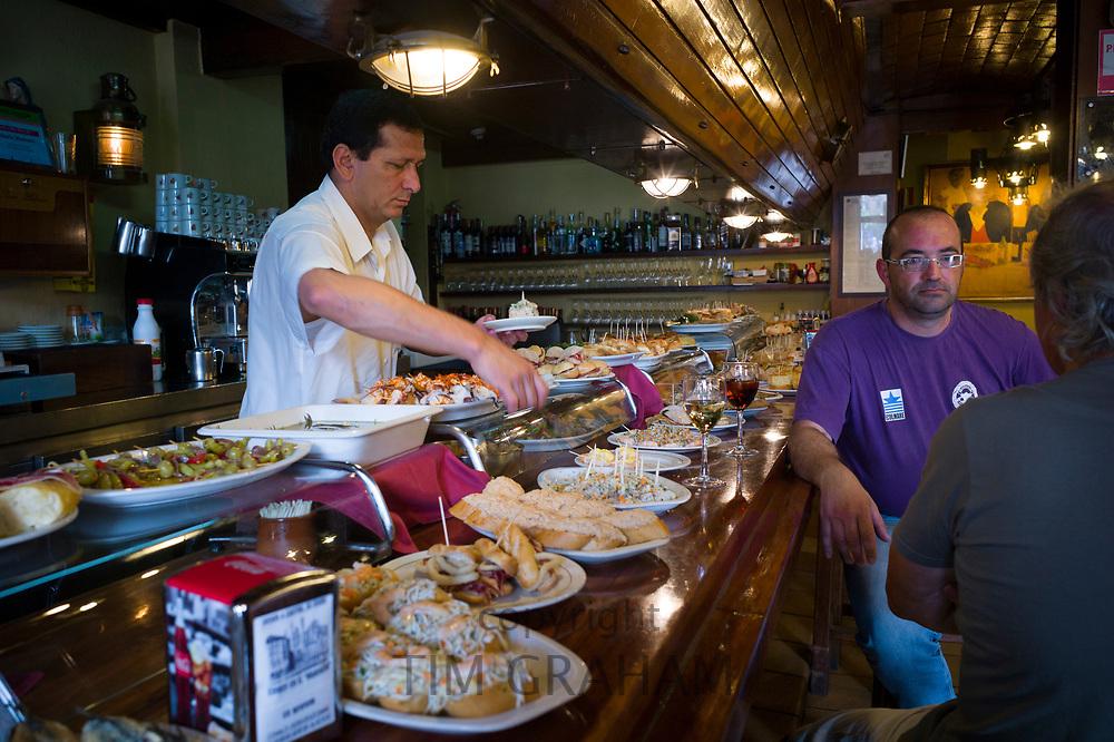 Tapas raciones being served in Taberna La Cierbanata  bar in Meson Marinero at Castro Urdiales in Cantabria, Spain