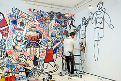 © Licensed to London News Pictures. 07/08/2021. LONDON, UK.  Ben Mosley, an action and expressionist painter, working on his wall mural focused on the achievement of Team Great Britain (GB) athletes at the Tokyo Olympics 2020.  Based at the pop-up Team GB Studio in Carnaby Street, he updates his mural daily with athletes' successes. The final day's events and closing ceremony are the only work remaining. Team GB has become the first to adopt non-fungible tokens (NFTs) featuring the athletes' previous achievements, which can be purchased through a dedicated store.  Photo credit: Stephen Chung/LNP