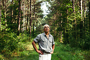 """MERIDIAN, MS – AUGUST 3, 2018: Clayton George, 57, walks under a canopy of mature Loblolly pine that is ready for final harvest. As a resident of Tennessee, George makes the four hour drive south every two weeks to check on his family's 400 acre tract, and visit his father who still lives there.<br /> <br /> In 1987, George and a friend walked in rows planting the family's first batch of Loblolly pine, where soybeans, wheat and cattle once covered the family's 400 acres.  The shift to timber was largely prompted by the Conservation Reserve Program, a popular new farm subsidy in the 1980s that encouraged farmers to reforest depleted land by paying them for every acre of trees planted. Since 1926, the George family had made a good living from their eastern Mississippi farm, but the decline of soybeans and other crops eventually led George to consider growing trees instead –a crop that landowners throughout the south believed would bring in easy money. Thirty years later, however, the same landowners are now facing unexpected financial hardship. Stumpage prices have been on a steady decline – as much as 45% since 2007 – and landowners are rethinking timber as a worthwhile investment. """"""""We figured we''d plant trees and come back and harvest it in 30 years, and in the meantime go into town to make a living doing something else,"""" George said. As co-owner of the family acreage with three other family members, George always considered himself the most nostalgic Now, as he patiently awaits for right time to harvest a 30 year investment, even he considers the future of the land uncertain. CREDIT: Bob Miller for The Wall Street Journal<br /> TIMBER_AL"""