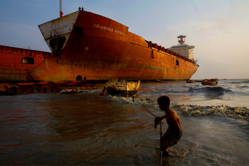 Ship breaking yards are the last resting place for end of life ships. At these yards, ships are scrapped, primarily for their steel content. <br /> Until 1980s, ship breaking took place in the developed countries such as the United States, UK, and Europe. Today, however, most ship breaking yards are in developing nations, principally Bangladesh, China, and India, due to lower labor costs and less stringent environmental regulations dealing with the disposal of lead paint and other toxic substances.<br /> Every year 600-700 sea vessels are brought to the beaches of Asia for scrapping and 52% of large ships are scrapped in Bangladesh.<br /> Workers have no unions, no safety equipment, and no training. About 50 are said to die in accidents each year; often in explosions set off by blowtorches deep inside the fume-filled holds. <br /> <br /> Children work in a ship breaking yard in Chittagong, Bangladesh.