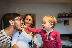 Little boy feeding his father with doughnut while mother is watching, Munich, Germany