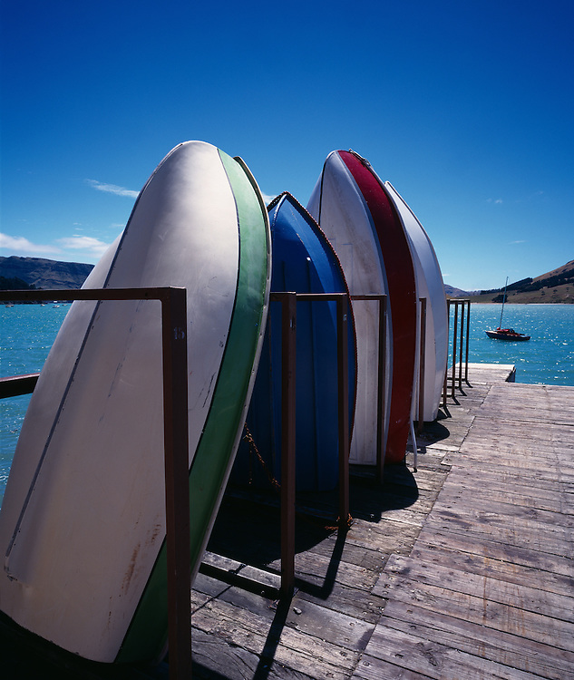 Dinghies standing up on dock with sailboat in distance in Sumner near Christchurch on the South Island of New Zealand