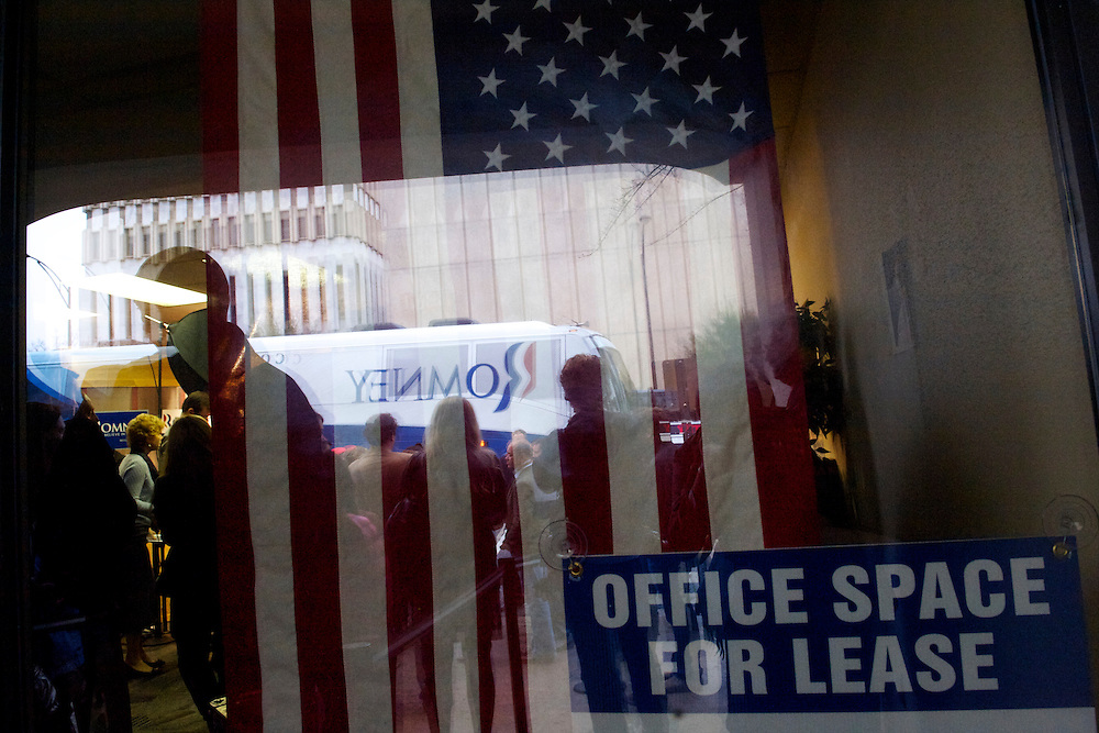The campaign bus of Republican Presidential candidate Mitt Romney and a mascot from a nearby tire store are reflected at a storefront next door to Romney Greenville campaign headquarters during his morning visit on the day of the South Carolina primary.