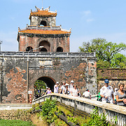 Tourists walk across a bridge over the moat from a guard tower at the Imperial City in Hue, Vietnam. A self-enclosed and fortified palace, the complex includes the Purple Forbidden City, which was the inner sanctum of the imperial household, as well as temples, courtyards, gardens, and other buildings. Much of the Imperial City was damaged or destroyed during the Vietnam War. It is now designated as a UNESCO World Heritage site.