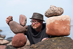 Dunbar, Scotland, UK. 20 April, 2019. Neil Andrews working on his stone sculpture on Eye Cave beach in Dunbar during opening day of the European Stone Stacking Championship 2019.
