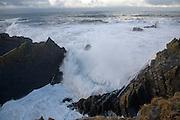 Large Atlantic storm waves crashing onto jagged rocky coast at Hartland Quay, north Devon, England