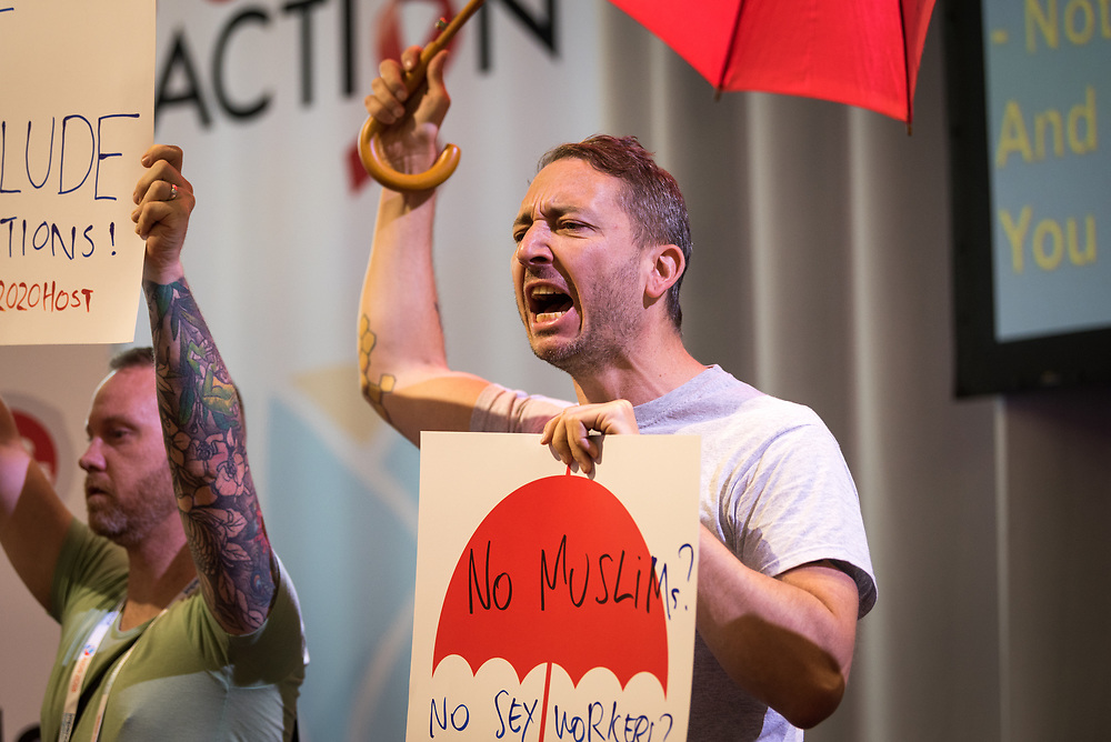 """26 July 2018, Amsterdam, the Netherlands: Demonstrators shout """"shame, shame, shame"""" as the Positive Flame, described as a """"torch of inclusion"""" is lit at the 2018 International AIDS Conference. The torch is to connect the 2018 conference with the 2020 conference, which is expected to take place in the United States, and the protestors, many of whom are sex workers or are part of other key populations, object because people from key populations as well as other groups, such as Muslims, may have difficilties getting a visa to travel to the United States. """"No conference in the United States, no conference in the United States,"""" they went on to chant. The Positive Flame is intended to travel from one International AIDS Conference to the next, and echoes the Olympic Flame that was introduced at the Olympic Games in Amsterdam in 1928."""