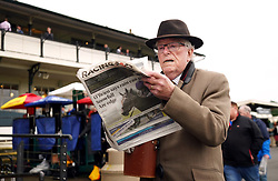 A racegoer checks the form in the Racing Post at Warwick Racecourse. Picture date: Thursday September 30, 2021.